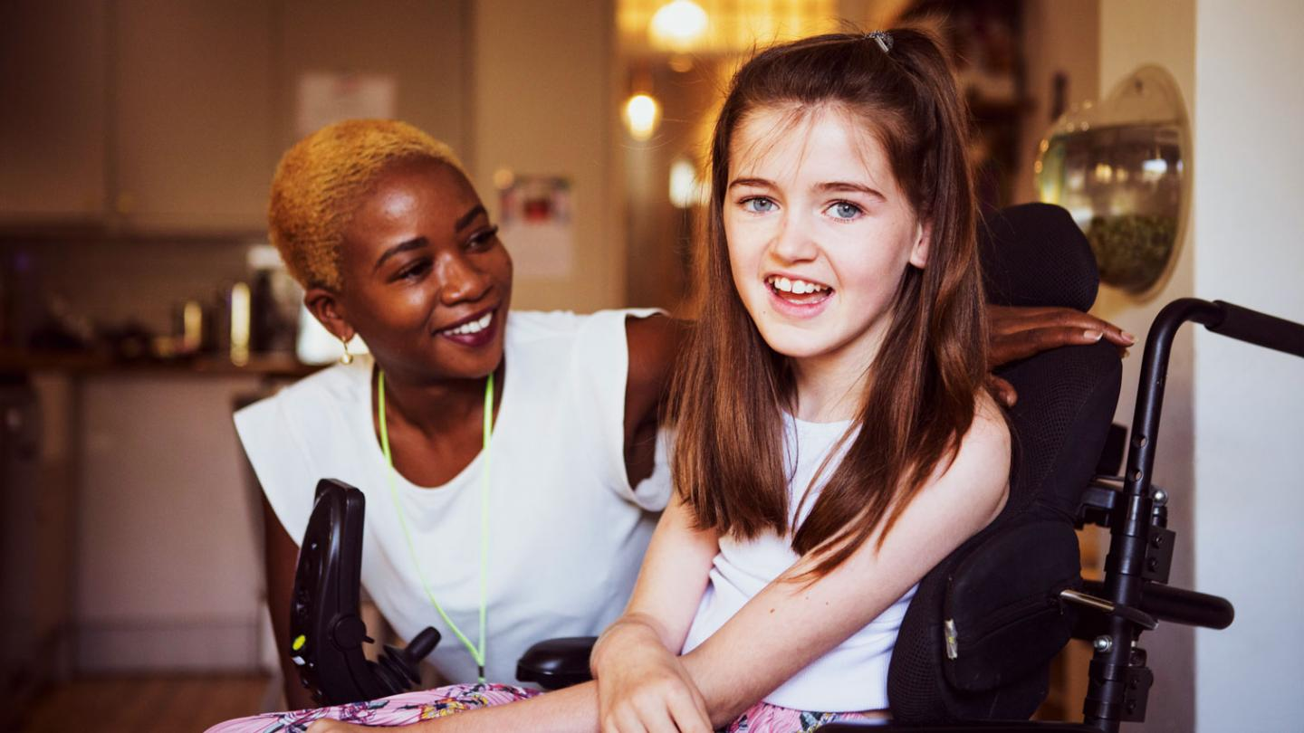 Young girl in a wheelchair smiling with her project worker