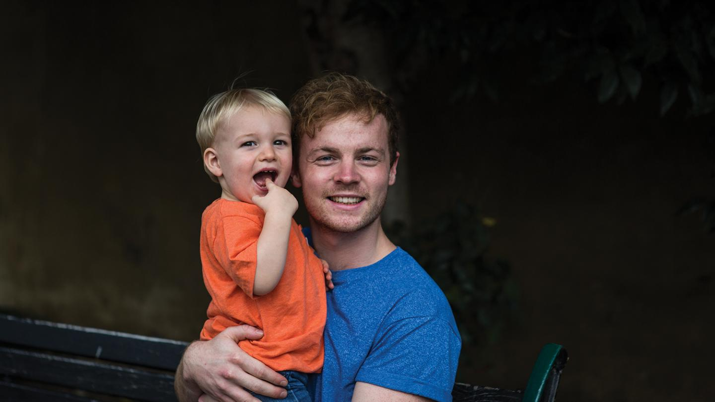 Adult male holding smiling boy