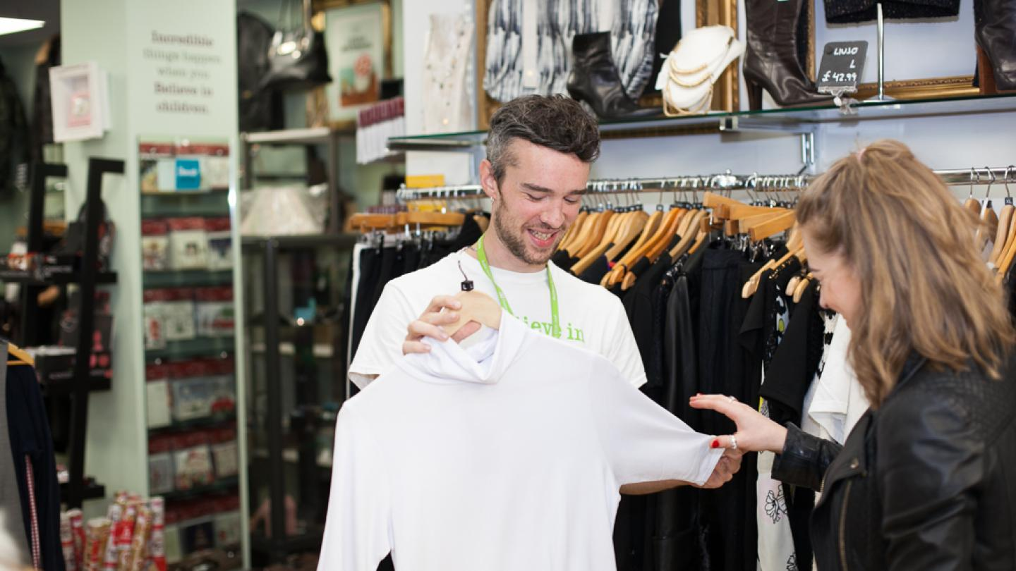 Volunteer shows a shirt to a customer in a Barnardo's charity shop