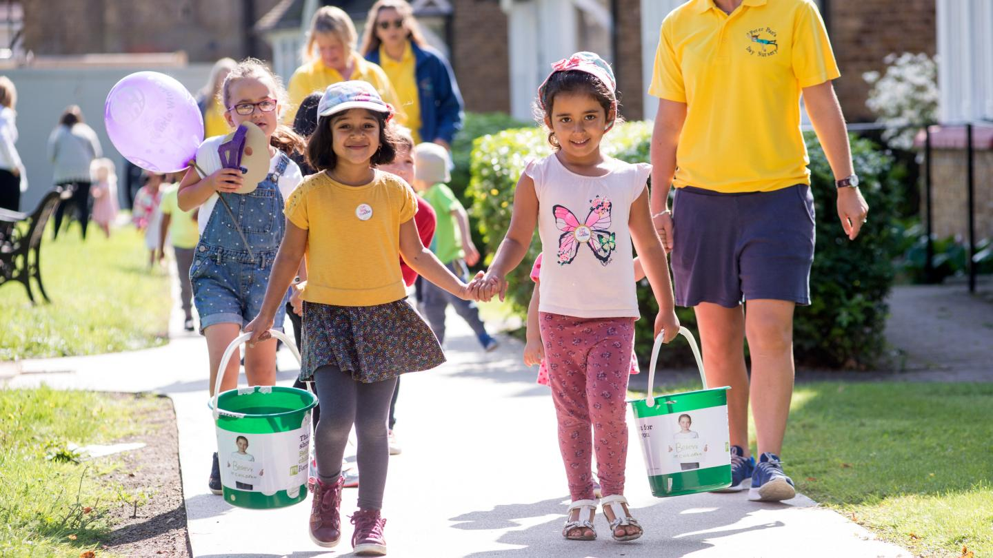 Two toddlers walking and holding hands carrying Barnardo's donation buckets
