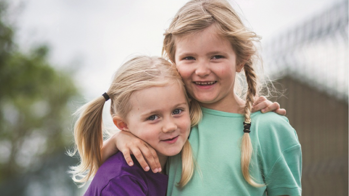 Two small girls smiling with their arms around each other