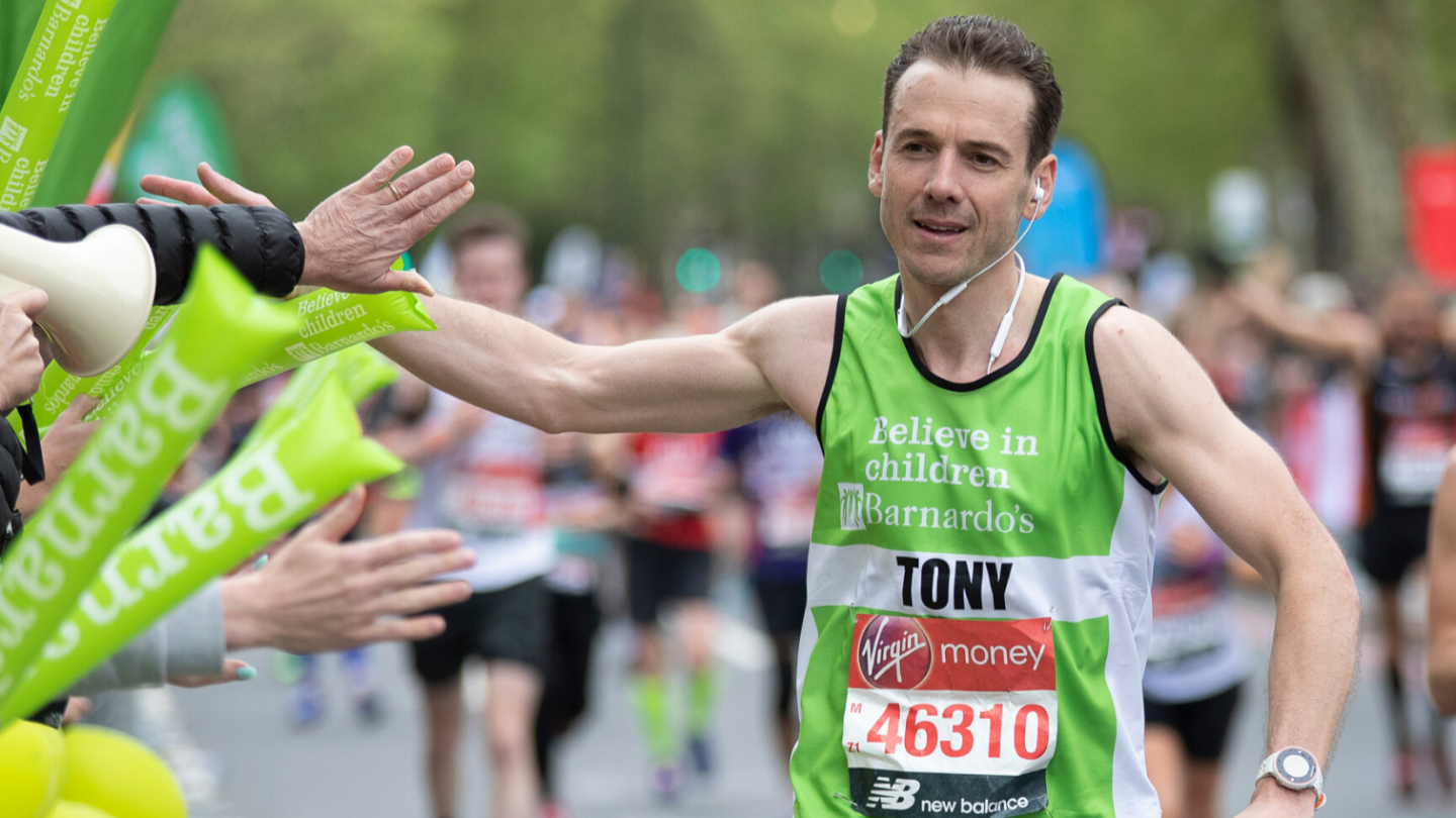 London Marathon runner high fiving people in the crowd