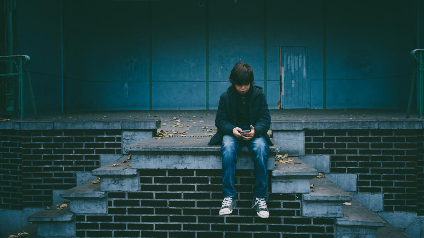 Boy sitting on wall looking at phone