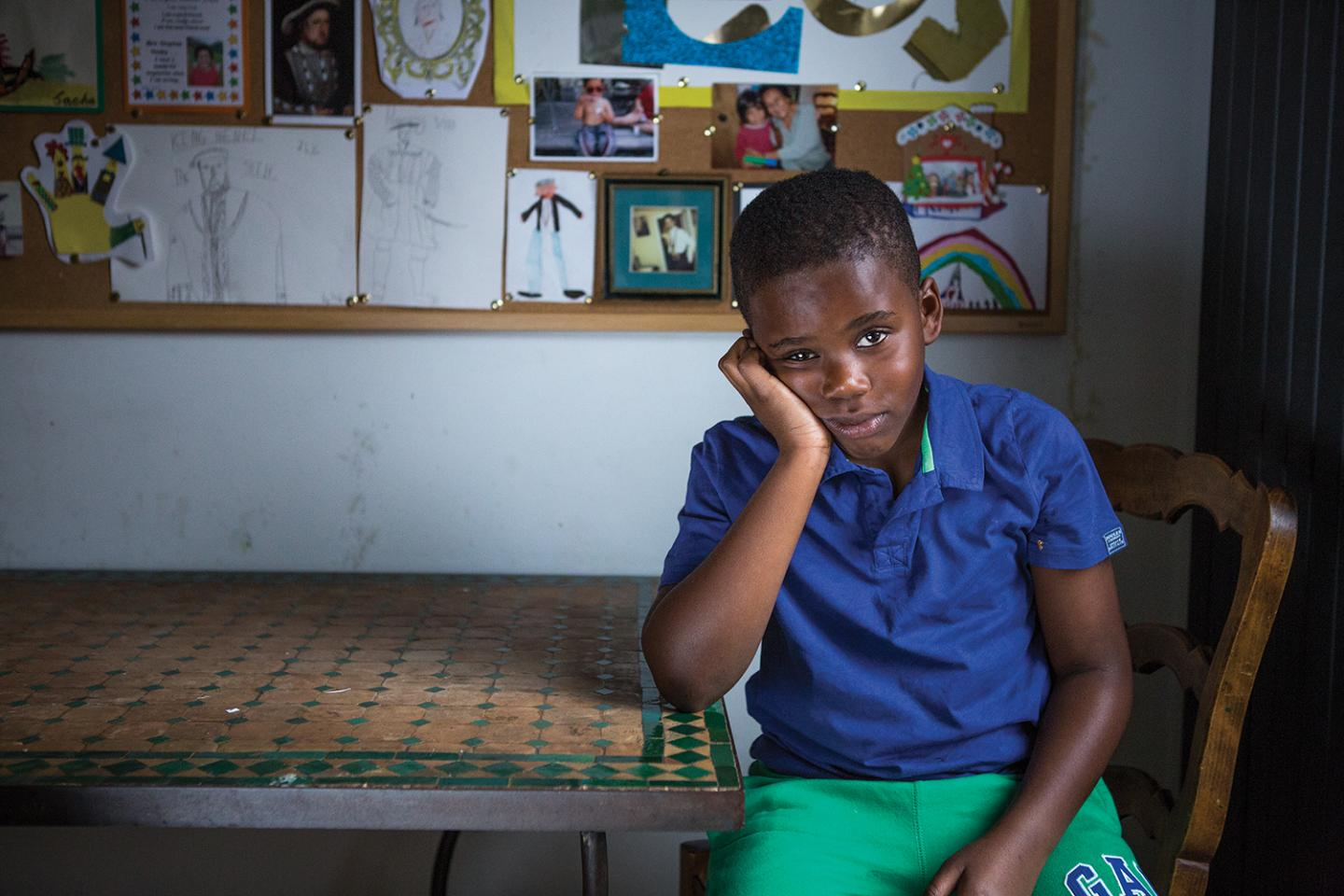 Young boy looking bored, leaning on a table