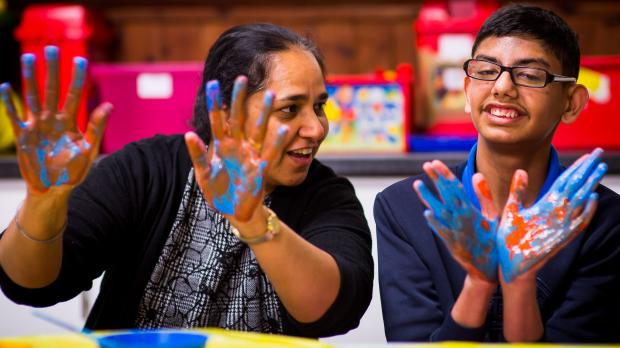 Boy and staff member using finger paints