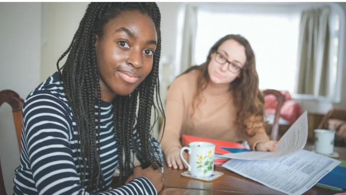 Teenage girl and foster carer sitting at a dining table