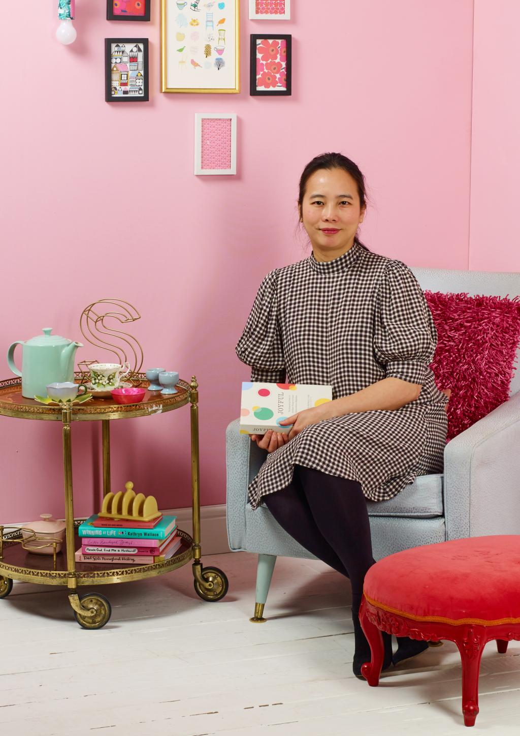Woman sitting in colourfully decorated loungeroom