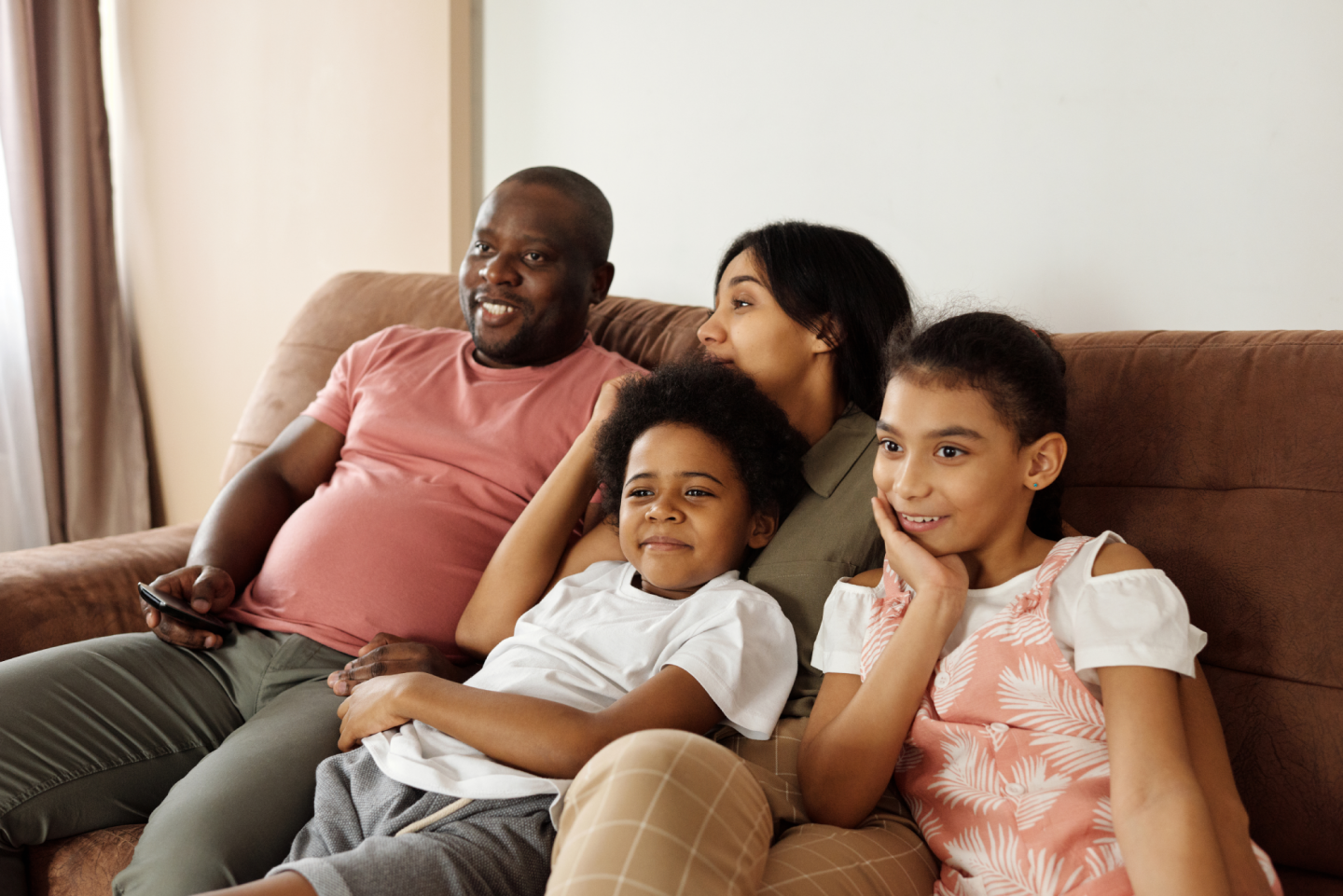 Family happily sitting on the couch watching tv