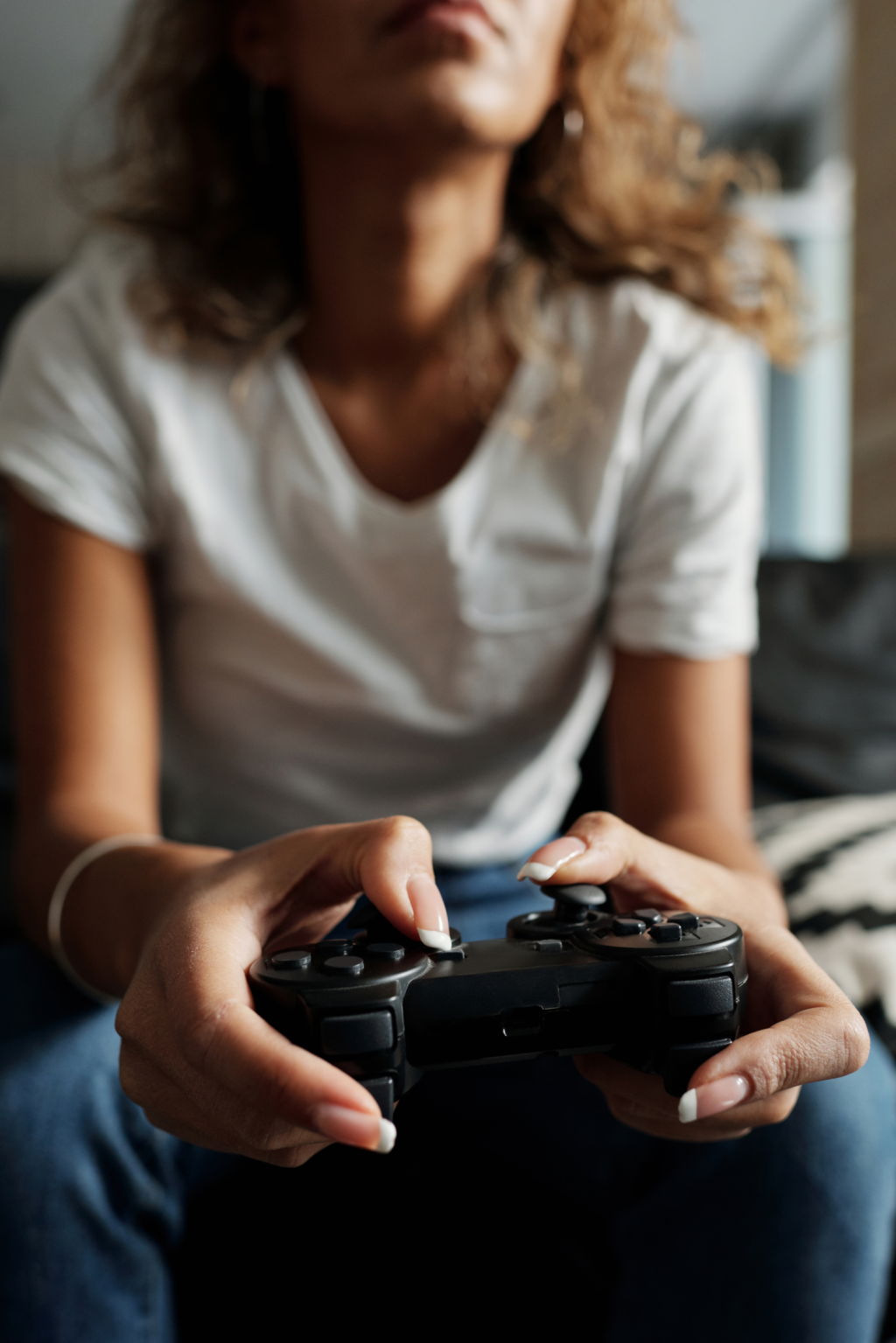 Person holding a playstation controller playing a video game