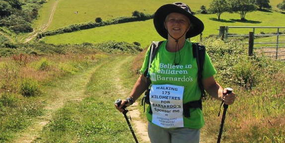 Woman completing a fundraising challenge standing in a sunny field