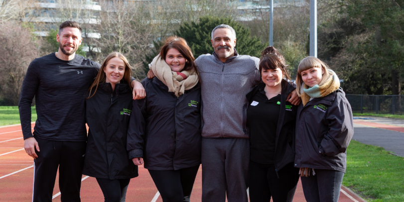 Daley Thompson and friends standing on a running track