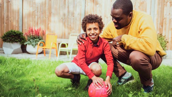 Young boy and foster carer playing with a football