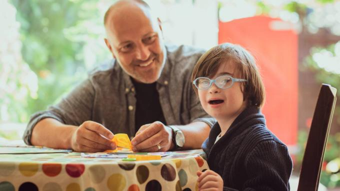 A young boy with downs syndrome sitting at a table with foster carer