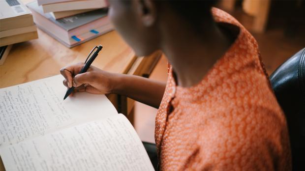 Child sitting at school desk writing