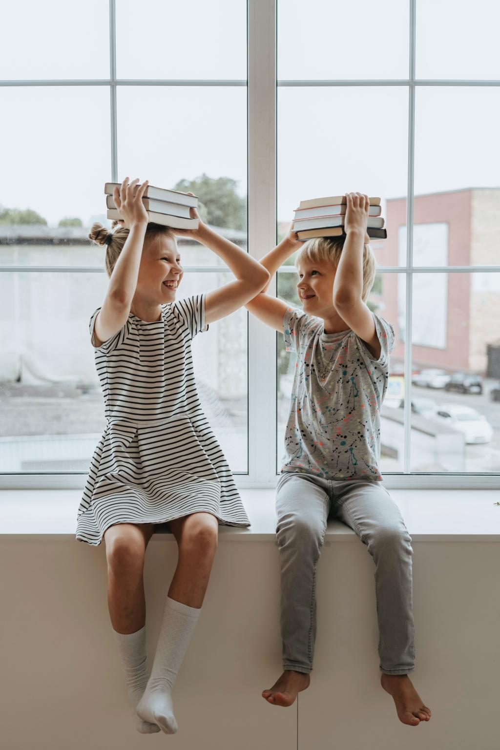 Children sitting on windowsill balancing books on head