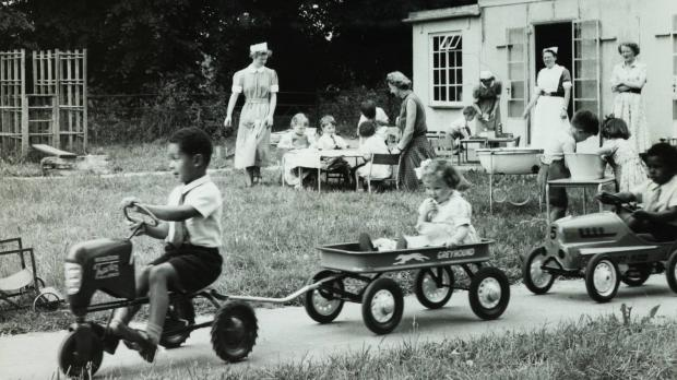 Children in toy cars at Oakley House