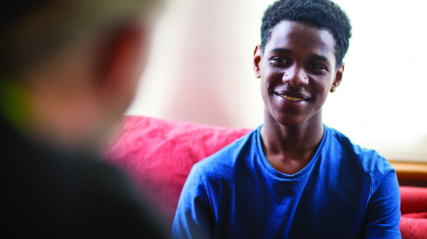 BAME young person in blue t shirt smiling