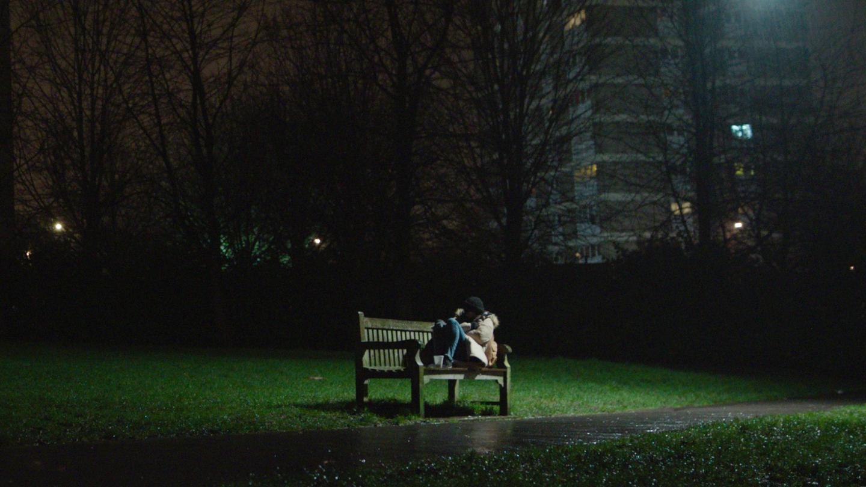 Girl sitting on park bench at night