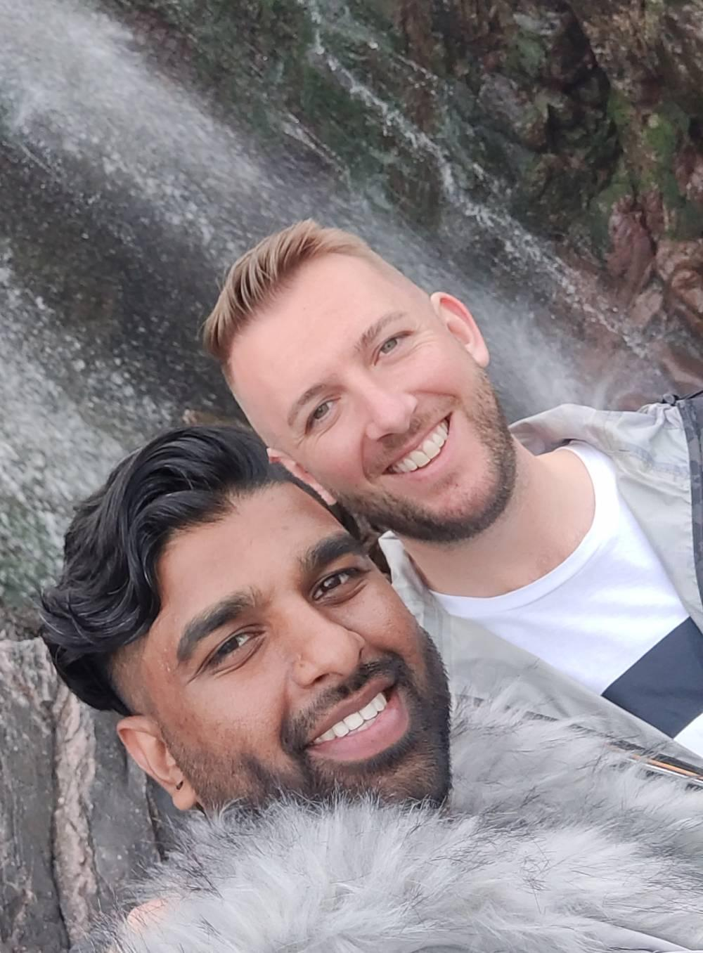 Two men standing in front of a waterfall