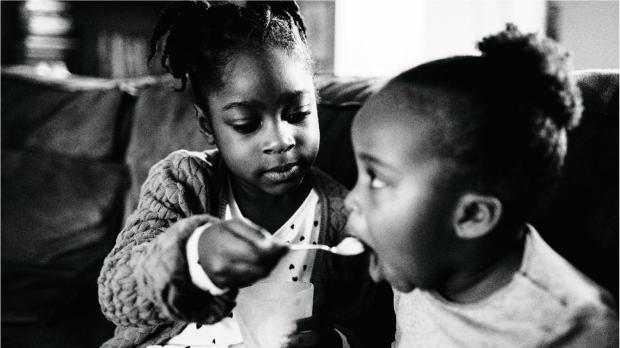 Girl feeding her younger sister