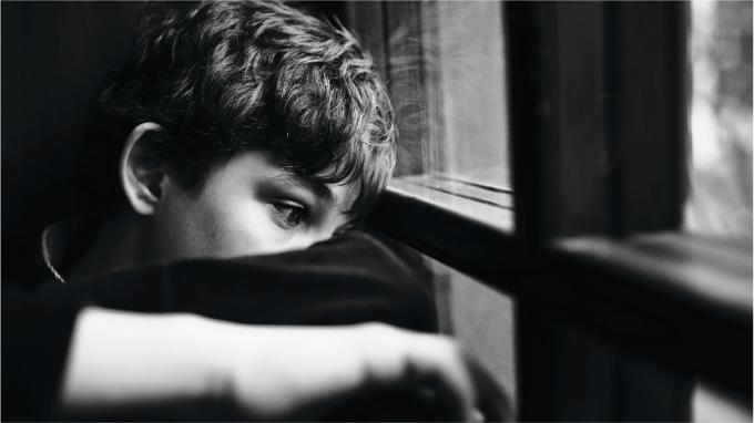Teen boy looking out window