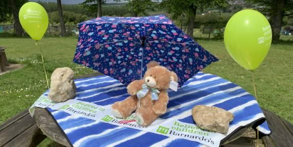 Teddy bear on a picnic table with balloons