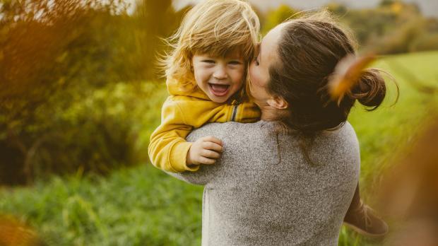 woman hugs child in a field