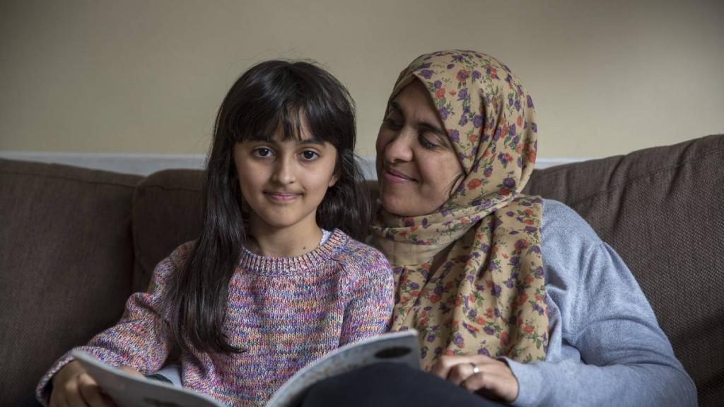 Muslim woman and child reading a book on a couch