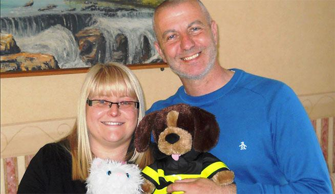 woman and man holding a plush toy dog
