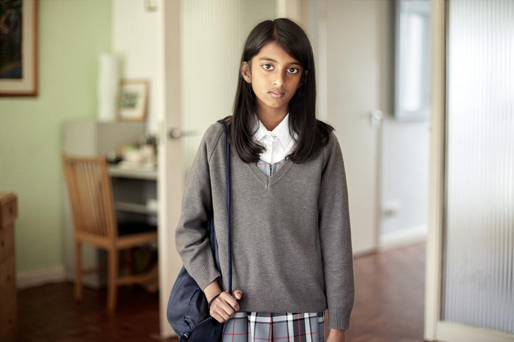 Young girl in school uniform with school bag on shoulder