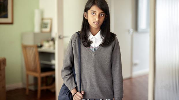 A young girl in a school uniform looking worried in a family living room