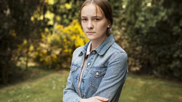 Young girl in denim jacket standing in garden