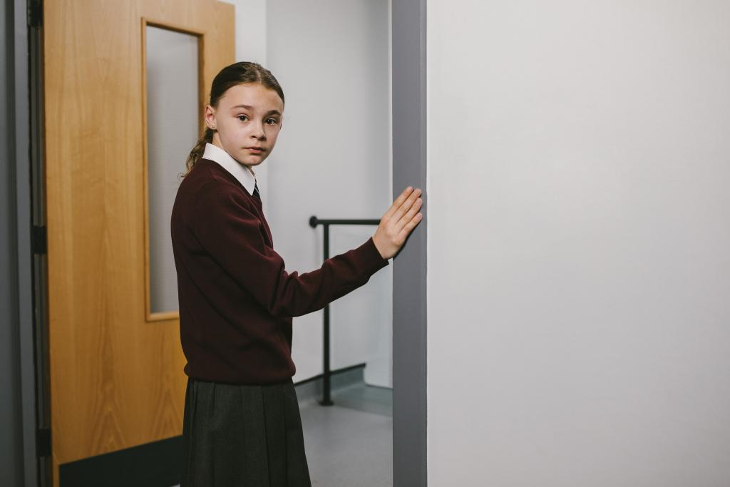 Young girl in school uniform going into class