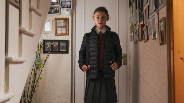 Young girl in winter coat stood in hallway