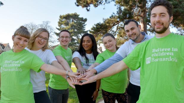 Group of Barnardo's employees reaching their hands into the centre of their group