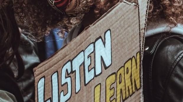 Protest sign: Listen, Learn