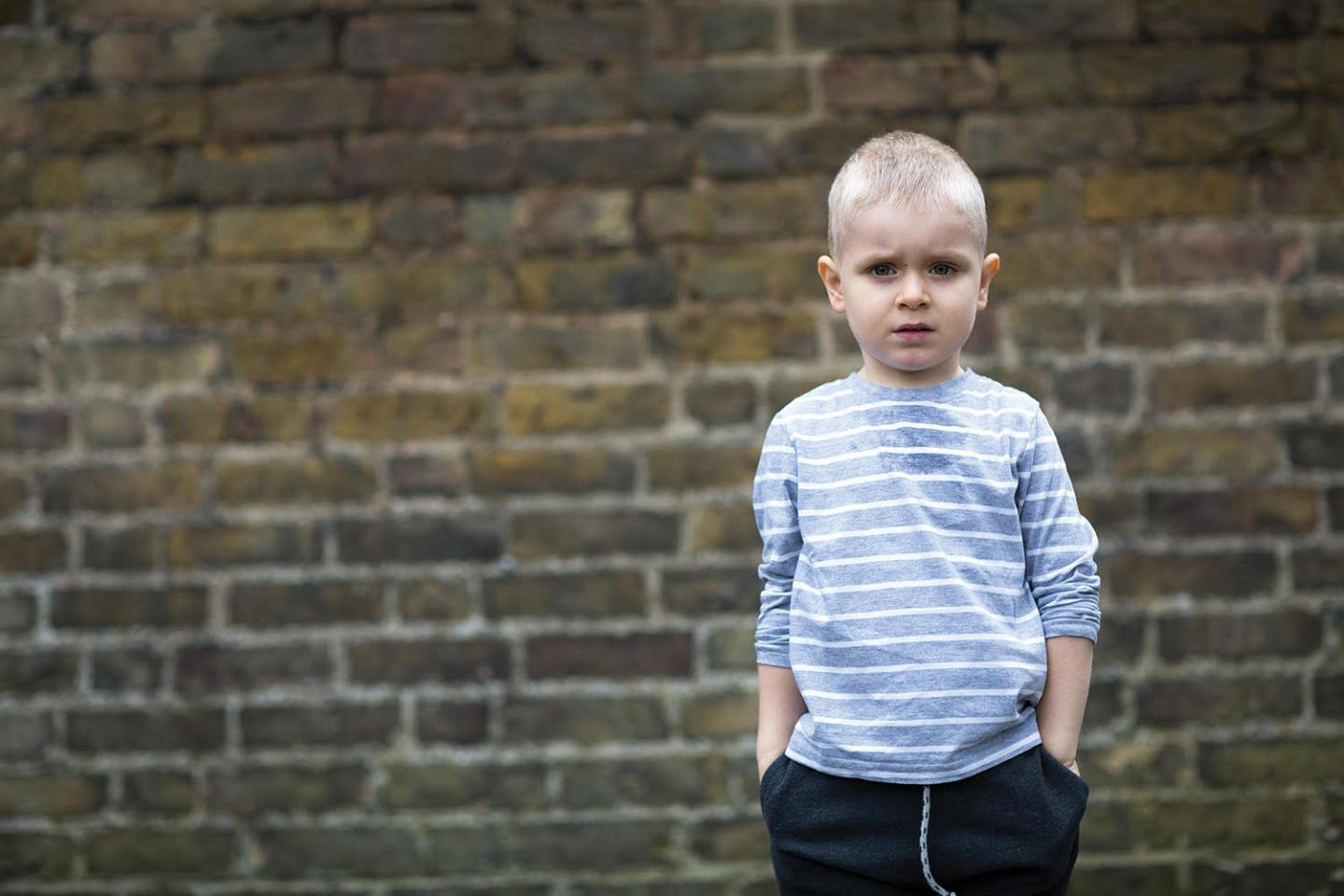 Young boy in front of a brick wall