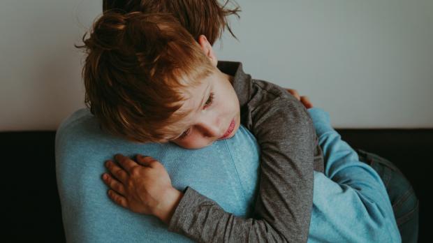 Stressed boy on parents shoulder