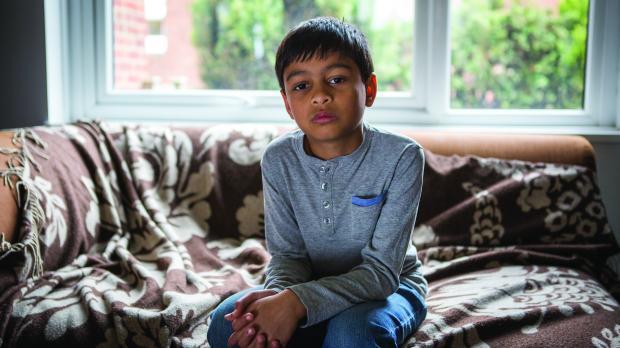 Young boy sitting on sofa