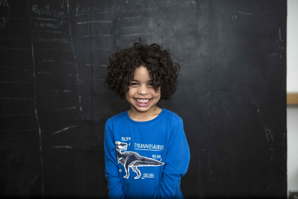 Smiling boy in front of blackboard