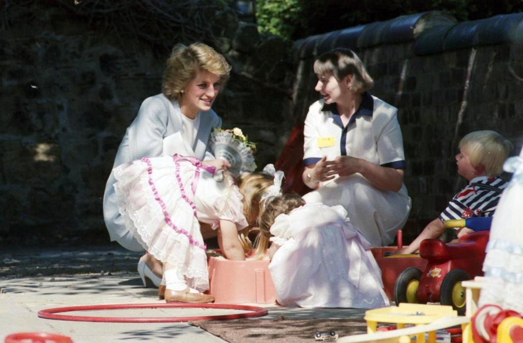 Princess Diana smiling and bending down to talk to a worker and children at a Barnardo's family centre