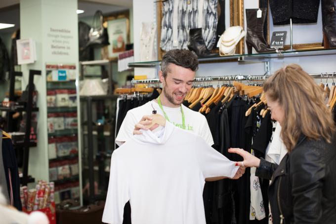 Shop volunteer holding up shirt while talking to customer