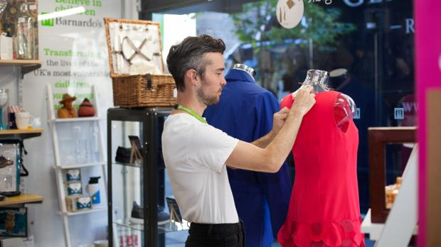Volunteer worker dressing a mannequin in a Barnardo's shop