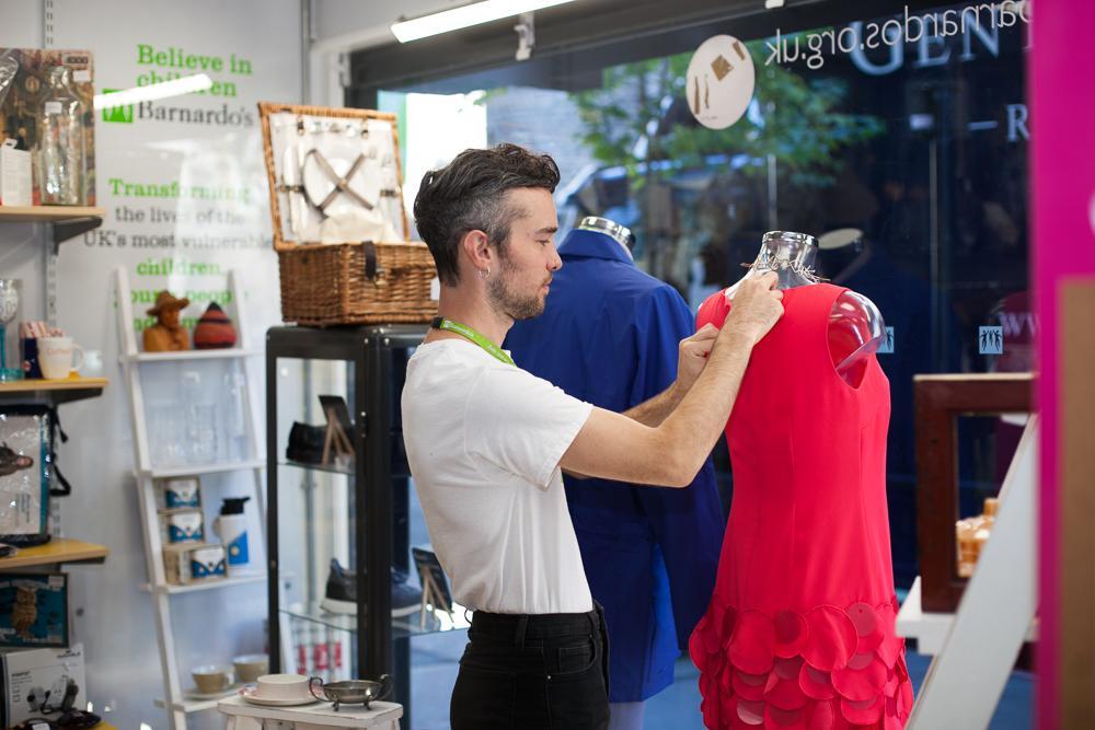 Man in Barnardo's shop dressing a mannequin