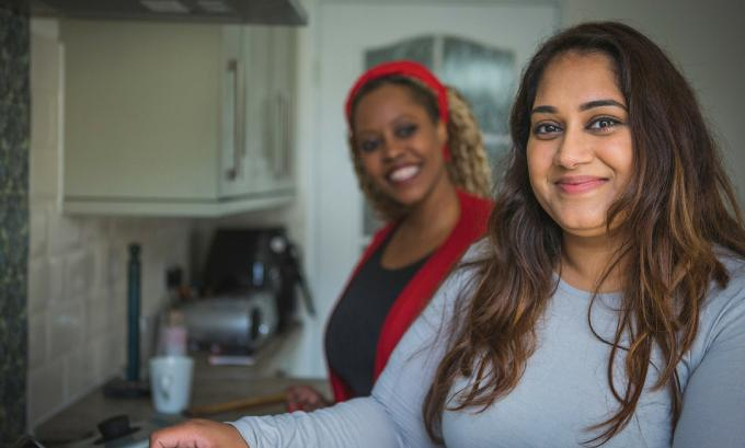Young person in kitchen with support worker in background