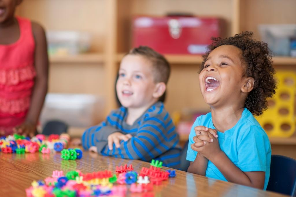 Laughing children playing with toys