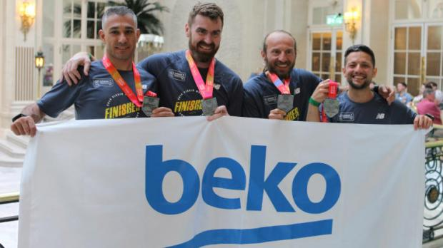 Beko employees holding up banner and their London Marathon medals