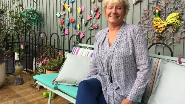 A foster carer sitting in her garden smiling