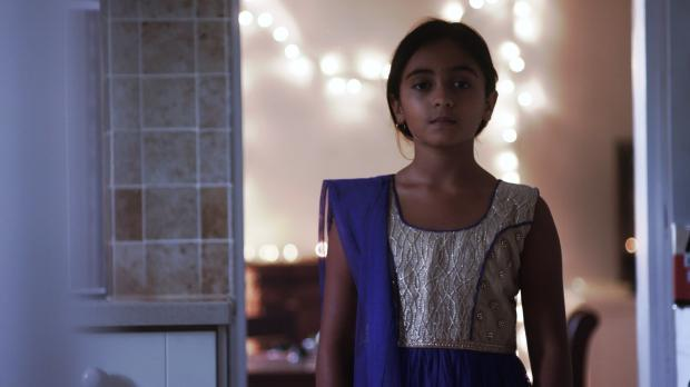 Young girl in house looking at camera with lights behind her