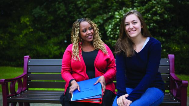 Support worker and young person sitting on park bench together.